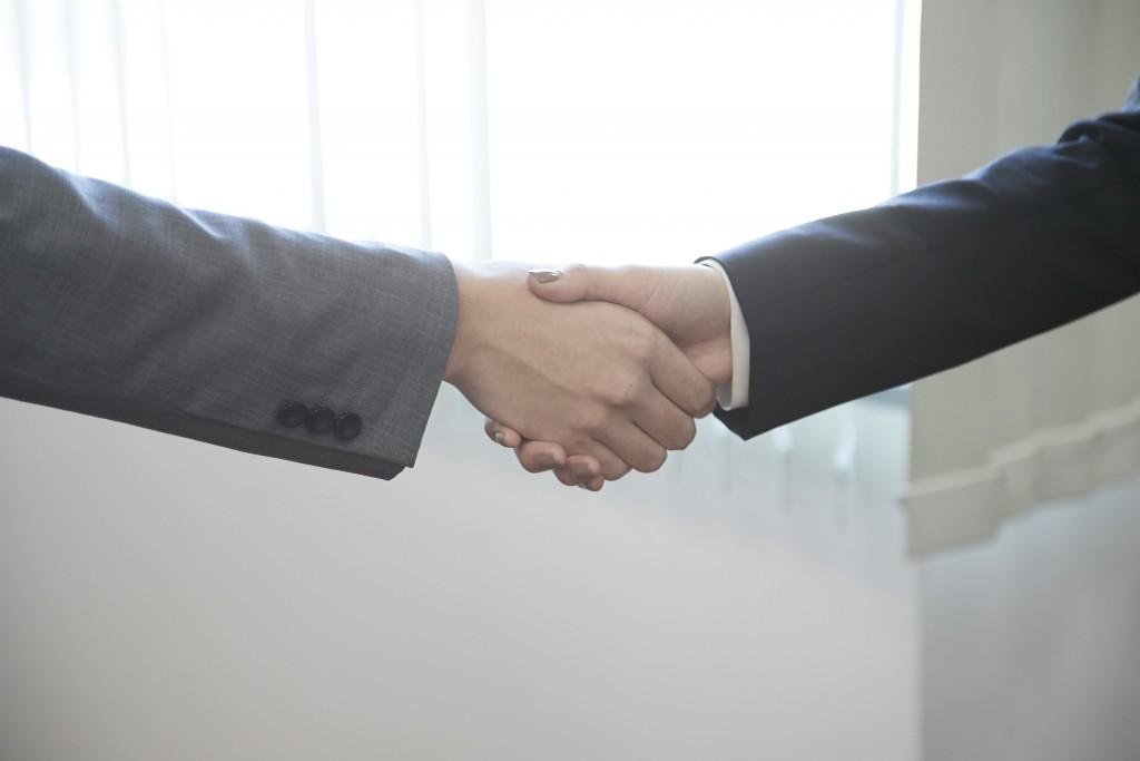 契約が決まって握手する写真